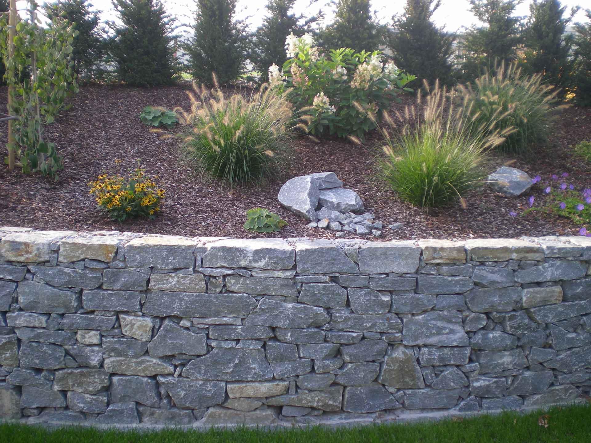 Natursteinmauer mit der Hand verlegt in Beton, Einfriedung, Alpengarten